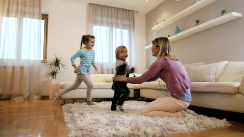 Joyful children running into mother's arms at home. Playful kids having fun with their mother in the living room while running in to her arms and embracing her. carefree stock videos & royalty-free footage