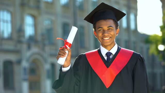 Joyful college student showing diploma celebrating graduation day, achievement