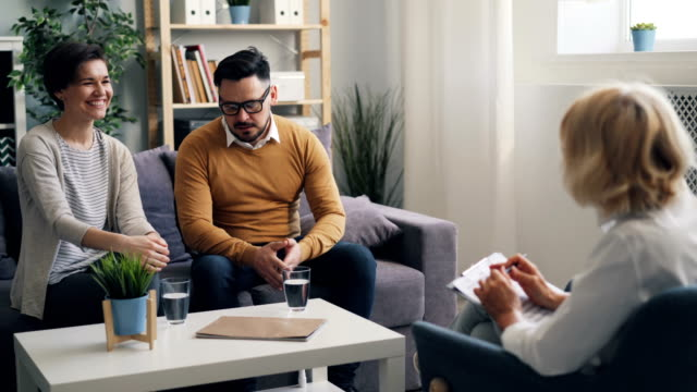 vídeos y material grabado en eventos de stock de alegre pareja hombre y mujer sonriendo hablando con psicoterapeuta durante el asesoramiento - consejo