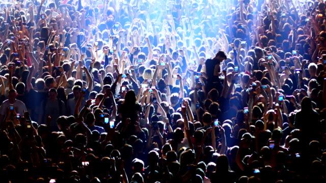 joyful crowd enjoys listening famous group rock concert