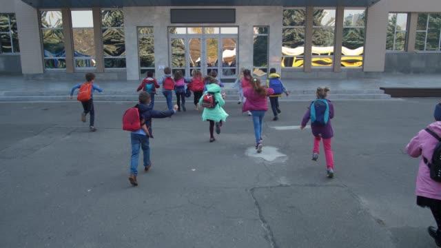 Joyful elementary age kids running to school doors