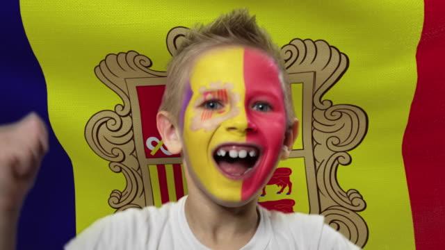 アンドラの旗の背景に喜びのファン。国の色で顔を塗った幸せな少年。 - サッカークラブ点の映像素材/bロール
