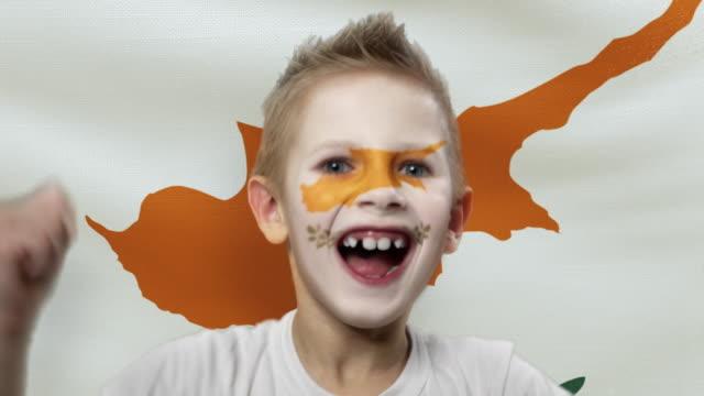 キプロスの旗の背景に喜びのファン。国の色で顔を塗った幸せな少年。 - サッカークラブ点の映像素材/bロール