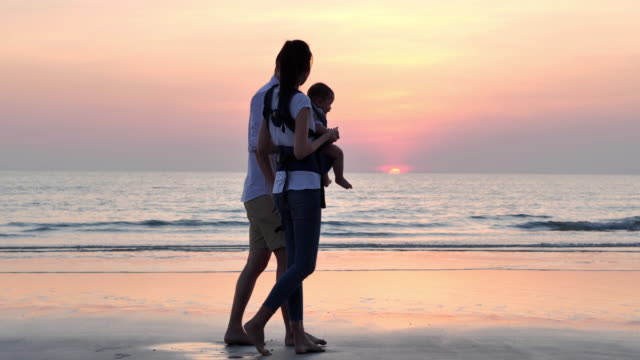 vídeos y material grabado en eventos de stock de padre alegre, madre, bebé hijo caminar con diversión a lo largo del borde de la puesta de sol surf de mar en la playa de arena. los padres activos y las personas actividades al aire libre en las vacaciones de verano con los niños. felices vacaciones en  - memorial day