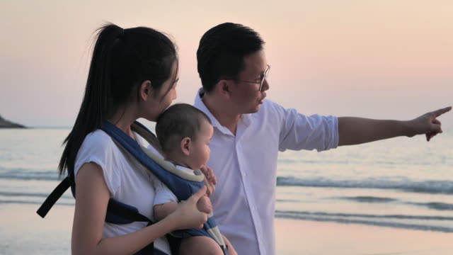 Joyful father, mother, baby son walk with fun along edge of sunset sea surf on sand beach. Active parents and people outdoor activity on summer vacations with children.Happy family holidays.Family,Lifestyle,People,Life insurance,Vacations - iStock video