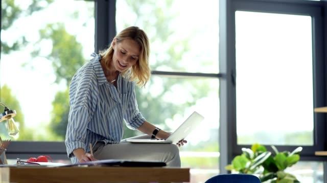 Alegre estudante feminino sentado na mesa, enquanto estudava on-line - vídeo