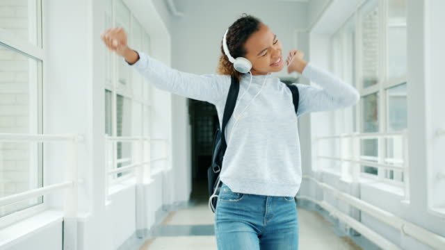 Joyful girl in headphones having fun in university hall singing dancing Joyful girl in headphones having fun in university hall singing dancing walking among students with backpacks. Modern lifestyle, happiness and devices concept. human age stock videos & royalty-free footage