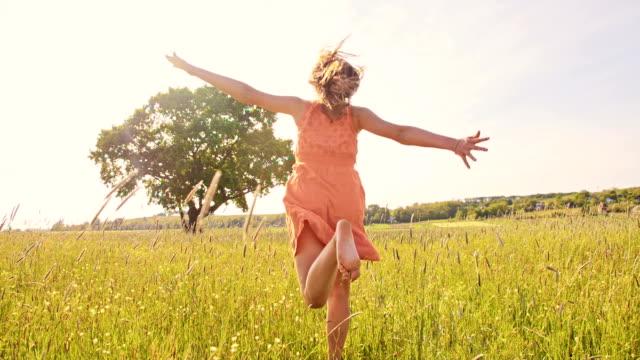 SLO MO Joyful girl running barefoot in the grass video
