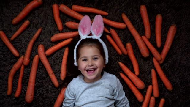 vidéos et rushes de fille joyeuse avec le costume d'oreilles de lapin - allongé sur le dos