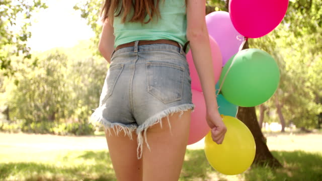 joyful girl with colourful balloons in a sunny park - young singles stock videos and b-roll footage