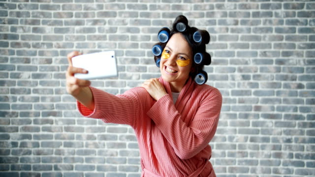 Joyful girl with hair rollers and eye patches taking selfie with smartphone