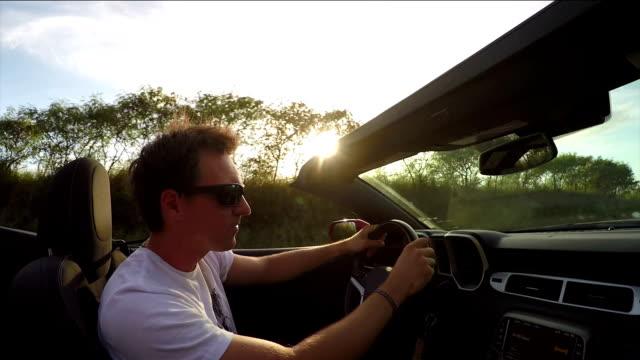 vidéos et rushes de close up: guy joyeux conduite en cabriolet de luxe, la musique et la danse - homme faire coucou voiture