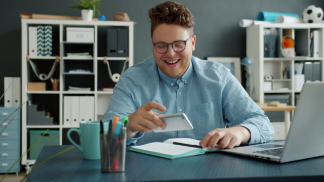 Joyful guy getting good news on smartphone spinning on chair in office kissing mobile Joyful guy employee is getting good news on smartphone spinning on chair in office kissing mobile celebrating success. Communication and lifestyle concept. chair stock videos & royalty-free footage