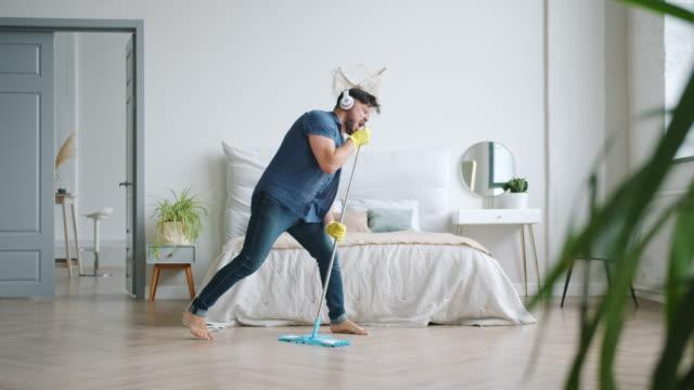joyful guy i hörlurar sjunger i mop tvätt golvet hemma ha kul - golv bildbanksvideor och videomaterial från bakom kulisserna