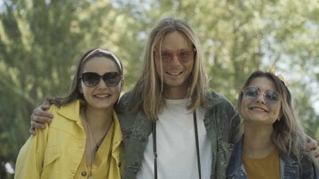 Joyful hippie man hugging cheerful women and smiling at camera. Portrait of three positive retro people in sunglasses posing outdoors on sunny summer day. 1960s lifestyle and pacifism.