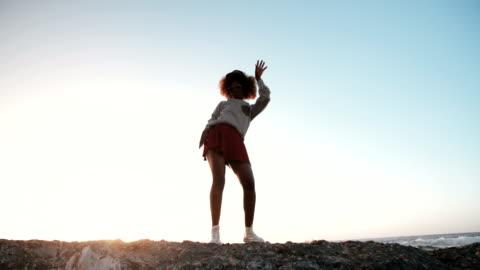 vidéos et rushes de hipster joyeux teen danse sur les rochers avec les bras avec passion - jeunes femmes