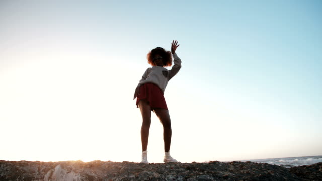 Joyful hipster teen dancing on rocks with arms out excitedly African American hipster teen dancing on some rocks at the seaside with her arms out excitedly in Slow Motion full length stock videos & royalty-free footage