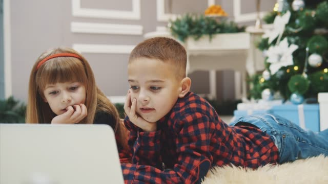 joyful kids are playing modern interesting games on laptop in room decorated for new year. - data scritta video stock e b–roll