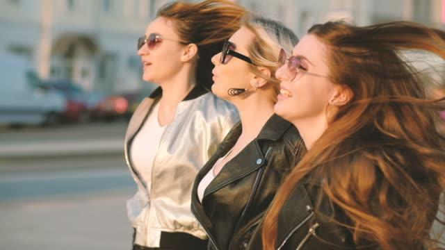 joyful ladies female friends enjoying urban sunset - city walking background video stock e b–roll