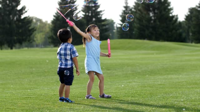 Joyful little asian kids playing with soap bubbles