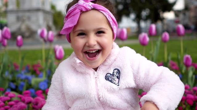 Joyful little girl throwing grass at the cameraman