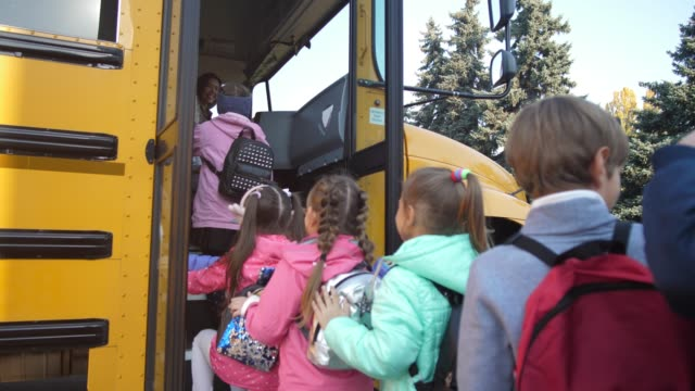 joyful little schoolchildren entering school bus - scolaro video stock e b–roll