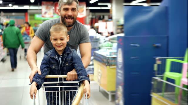 うれしそうな愛情のある父が彼はかわいい息子とスーパー マーケットで楽しいを持っている、人々 は笑っている、それの上に立って小さな男の子とショッピングカートで走っています。 - 小売り点の映像素材/bロール