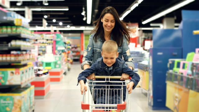Joyful loving mother is having fun in supermarket with her cute little son, she is running with shopping cart with small boy standing on it, people are laughing. Joyful loving mother is having fun in supermarket with her cute little son, she is running with shopping cart with happy small boy standing on it, people are laughing. woman pushing cart stock videos & royalty-free footage
