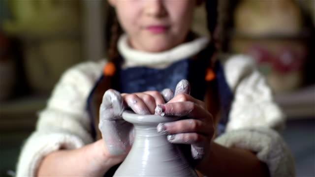 Joyful Maker Tilt up of a cute little girl making a clay jar on a pottery wheel  charming stock videos & royalty-free footage