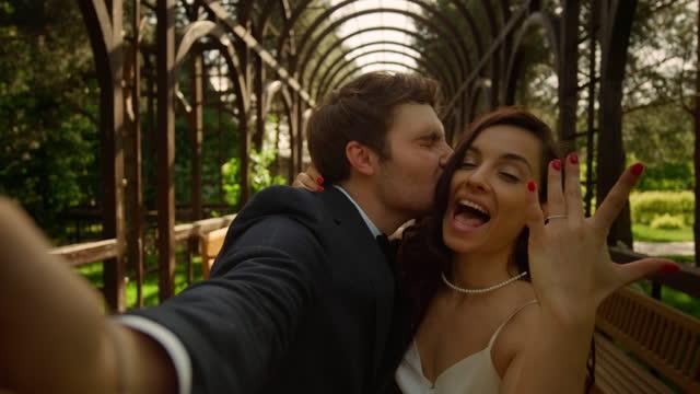 uomo e donna gioiosi che fanno selfie all'aperto. coppia sorridente sulla macchina fotografica nel parco - fidanzato video stock e b–roll