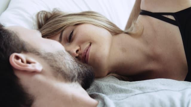 Homme et femme joyeux embrassant et détendant dans le lit - Vidéo