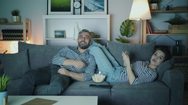 Joyful man and woman watcing TV throwing popcorn laughing in house at night
