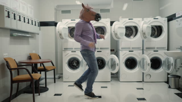 joyful man in mask horse dancing cheerful in laundry room. man dancing viral dance and have fun in laundry room. happy guy enjoying dance, having fun together, party halloween. slow motion. halloween - tiktok стоковые видео и кадры b-roll