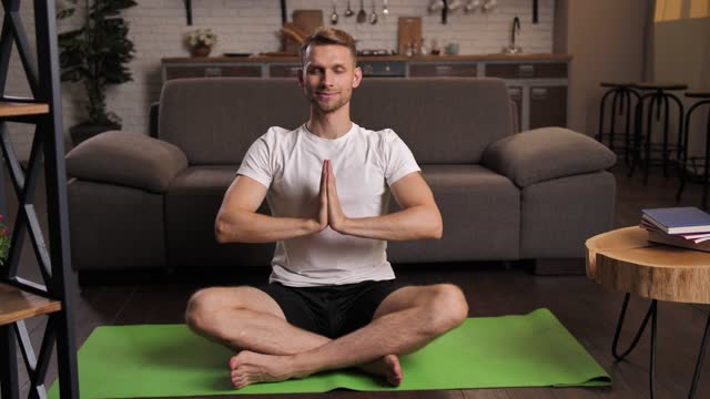 Joyful man meditating in yoga lotus pose at home Closeup of smiling handsome male practicing meditation on yoga mat in domestic interior during coronavirus lockdown. Cheerful athletic man closing his eyes while relaxing in yoga lotus position indoor lotus position stock videos & royalty-free footage