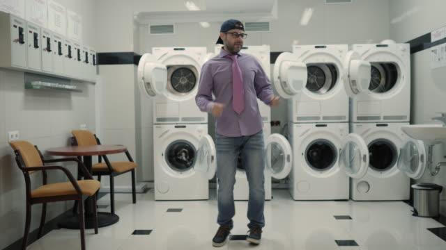 帽子のひげと洗濯室で陽気に踊る眼鏡を持つ喜びの男。男はウイルスダンスを踊り、洗濯室で楽しんでいます。ダンスを楽しむハッピーガイ、一緒に楽しんで、パーティー。スローモーショ� - 楽しい 洗濯点の映像素材/bロール