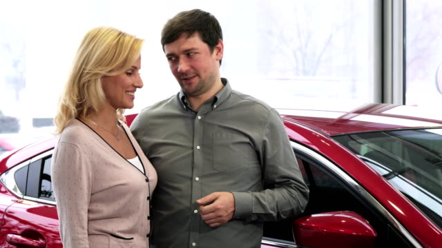 Joyful mature couple showing car keys and thumbs up after buying a new auto video