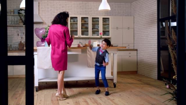 stockvideo's en b-roll-footage met vrolijke mixed race familie dansen in de keuken - mid volwassen vrouw