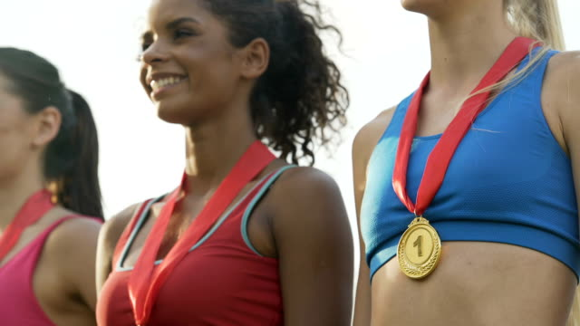 Joyful multiracial girls standing on podium, proudly showing medals on chests video