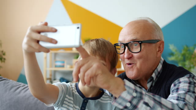 Joyful people old man and boy taking selfie at home posing smiling using smartphone video