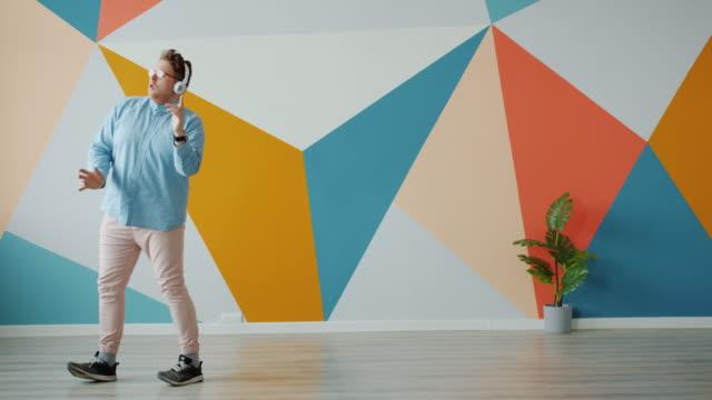 Joyful person dancing indoors wearing headphones enjoying pop music at home