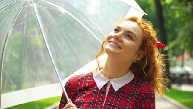 joyful red haired girl walking in sunny park with umbrella - nastro per capelli video stock e b–roll