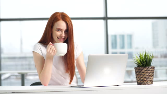 Joyful redhead girl sitting by table with laptop and looking in camera video