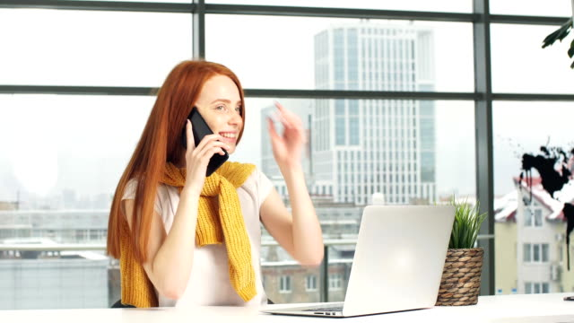 Joyful redhead girl, working in the office, uses a laptop and mobile phone video