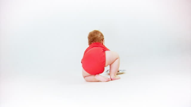 Fröhliche Szene auf weiß. Baby spielt mit Gabel und Löffel. – Video