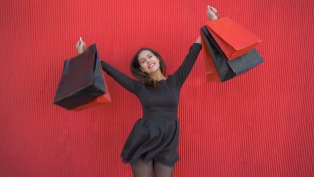 vídeos y material grabado en eventos de stock de chica alegre comprador levanta bolsas de compras hasta danzas de felicidad a negro el viernes de venta estacional - black friday sale