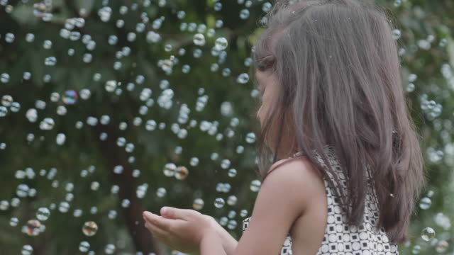 Joyful siblings playing with soap bubbles at park. video