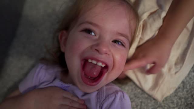 Joyful smiling toddler girl enjoying playful time with her family