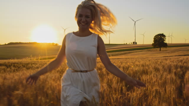 MS Joyful woman caressing wheat plants while running in a field with wind turbines in the distance Medium shot of a mid adult woman caressing wheat plants with her hands while running toward the camera in the middle of a field of golden wheat with wind turbines in the distance. Shot taken at sunset. Shoot in 8K resolution. mid adult stock videos & royalty-free footage