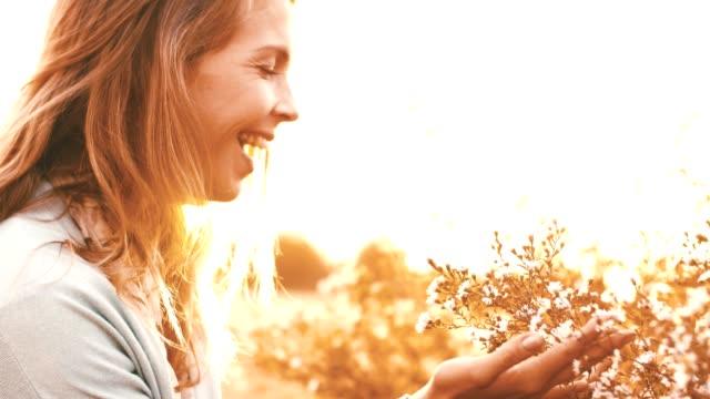 Joyful woman enjoys flowers in the field