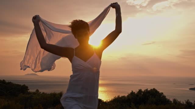 slo mo веселая женщина держит шаль in the wind - шарф стоковые видео и кадры b-roll